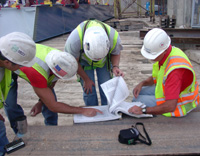 Engineers with hard hats viewing construction materials