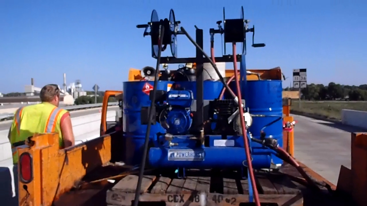 using blue tanks on an orange truck to seal bridge decks efficiently