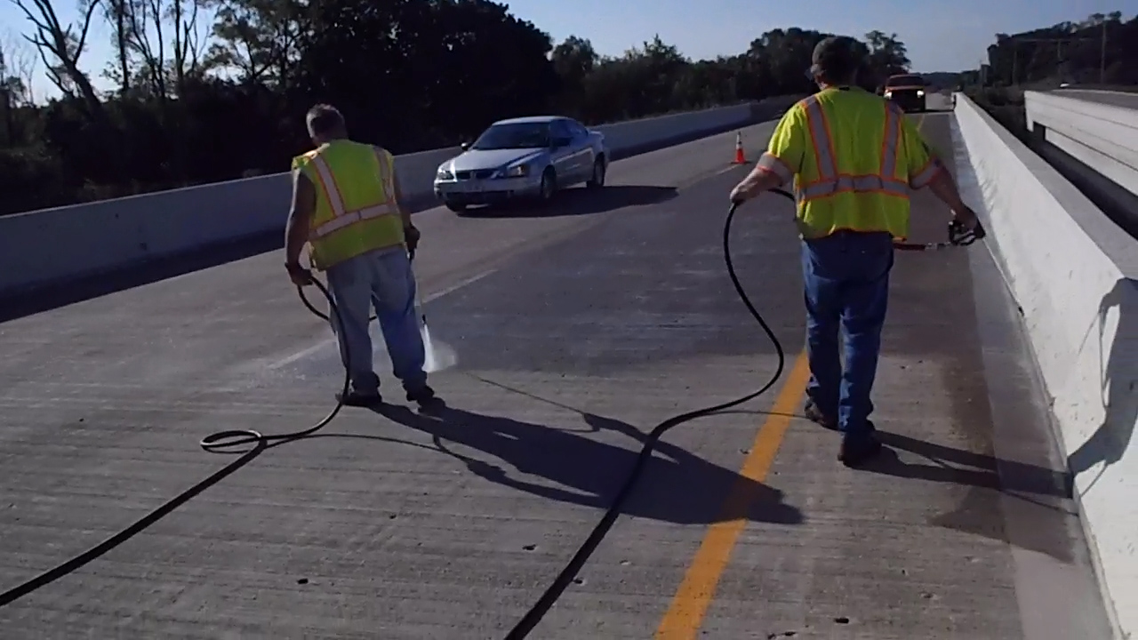 workers sealing a bridge deck with hoses