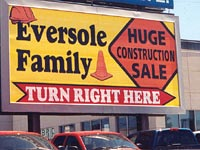 "A large billboard that reads, ""Eversole Family, Huge construction sale, turn right here"""